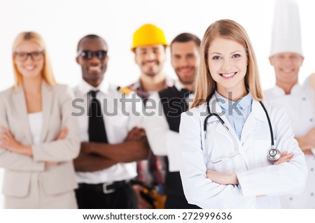 When I grow up I will be a doctor. Beautiful young female doctor keeping arms crossed and smiling while group of people in different professions standing in the background - stock photo