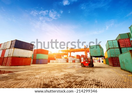 When the container terminal at dusk, work cranes and forklift. - stock photo