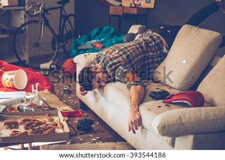 When the party is over. Young handsome man passed out on sofa in messy room after party - stock photo