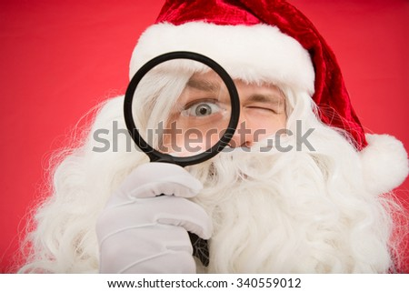 Where are all the good kids. Closeup portrait of Santa Claus looking through a magnifying glass - stock photo