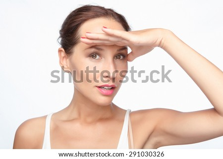 Where are you. Waist up portrait of a beautiful woman with brown hair looking for someone or something holding a hand near her forehead, isolated on white background - stock photo