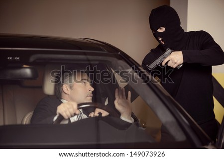 Where is the money? Men in black balaclava holding gun and aiming a shocked mature businessman sitting on the front seat of a car - stock photo