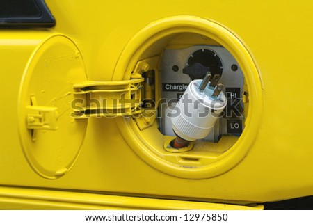 Where the gas tank is usually, there is a plug in this yellow electric car - stock photo