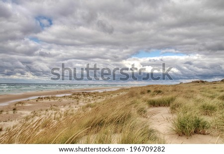 Where The Horizon Meets The Sky. Remote beach with storm clouds rolling in over the windswept dunes. Ludington State Park. Ludington, Michigan.  - stock photo