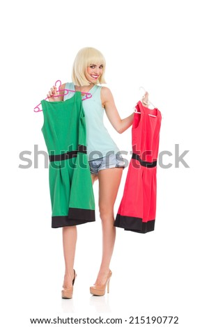 Which dress should I take? Happy blond young woman holding green and red dress on hanger. Full length studio shot isolated on white.