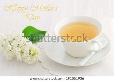 While lilac with cup of tea on rustic white cutting board for a Happy Mother's Day