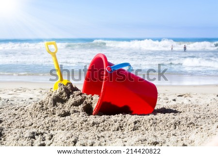 While playing in the water, a child??s toy plastic bucket and shovel are left in the sand during a summer holiday. - stock photo