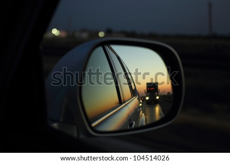 While traveling on a highway the reflection of a semi-trailer truck on the right side mirror of an SUV during sunset. - stock photo