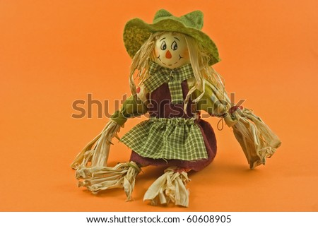 Whimsical corn husk farmer's wife doll on orange background with copy space in horizontal format - stock photo