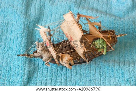 Whimsical fantasy voyage with toy 3 mast sailing ship and ceramic cat dog and frog shot from above. - stock photo