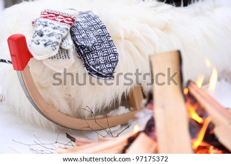 Whine rug and two pairs of mittens on sled close to bonfire on sunny winter day in forest. - stock photo