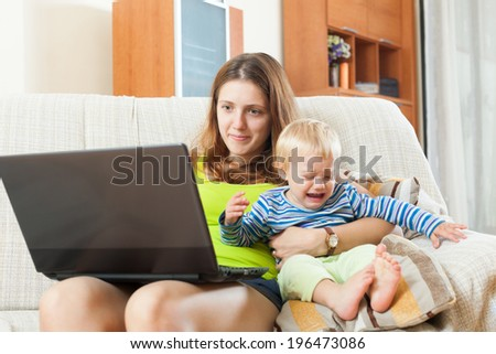 Whiner young mother with a crying baby, working with a computer at home - stock photo