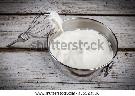 Whipped cream in bowl with and whisk - stock photo