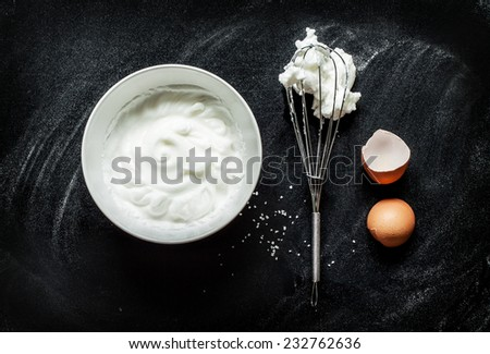Whipping an egg whites into a foam recipe - composition on black chalkboard from above. Simple modern kitchen poster design with white bowl, eggbeater and eggshell. - stock photo