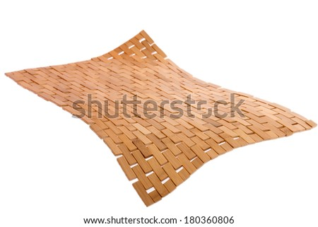 Whirling bamboo mat floating in the air isolated on white with a diagonal perspective and corner bent down in the foreground showing weave and texture detail - stock photo