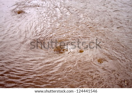 Whirlpools on a dirty river - stock photo