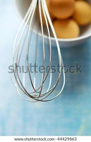 whisk and brown eggs in bowl