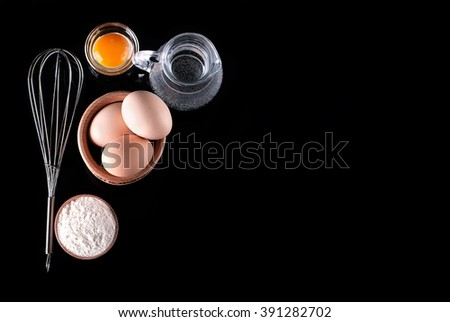 whisk and ingredients on a black background - stock photo