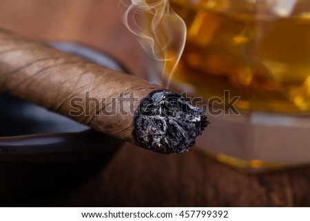 Whiskey and cigar on wooden background