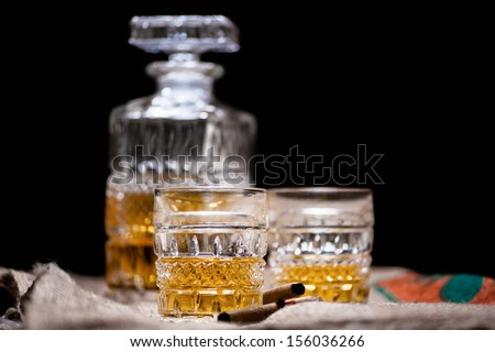Whiskey and scotch drinks on wood with bar bottle on background isolated on black - stock photo