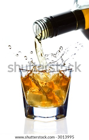 Whiskey being poured into a glass against white background