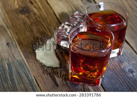 Whiskey drinks with ice on old wooden table. retro style - stock photo