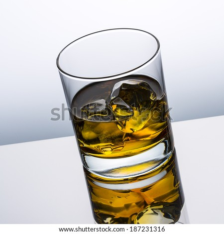 whiskey glass alcohol with ice cubes rocks with reflection drink Scottish and grey gradient background
