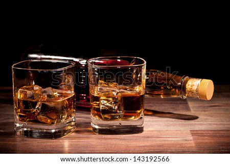 Whiskey glass on wooden table - stock photo
