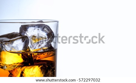 Whiskey glass with three ice cubes on white glass surface over white background