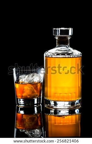 Whiskey on the rocks and a whiskey bottle in dark background - stock photo