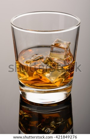 Whiskey on the rocks in the glass. Close up. Whisky with ice - stock photo