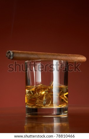 Whiskey with ice cubes and cigar, on brown background - stock photo