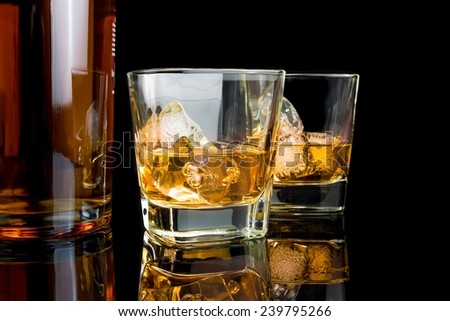 whiskey with ice in glasses near bottle on black background, with reflection - stock photo