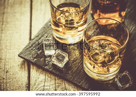 Whiskey with ice in glasses, rustic wood background, copy space - stock photo