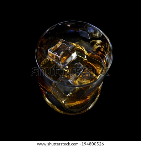 Whiskey with ice in simple glass on  black background - stock photo