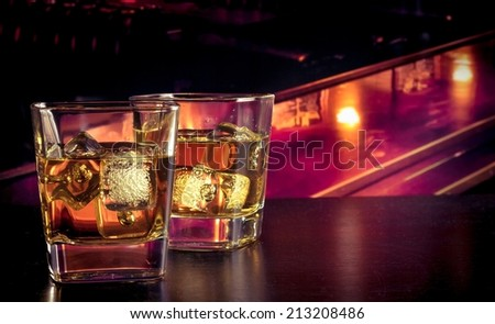 whiskey with ice on bar table lounge bar atmosphere - stock photo