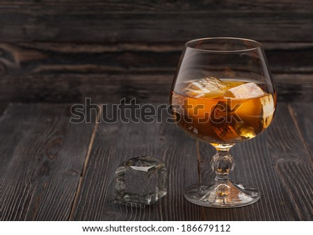 Whiskey with ice on dark wooden background  - stock photo