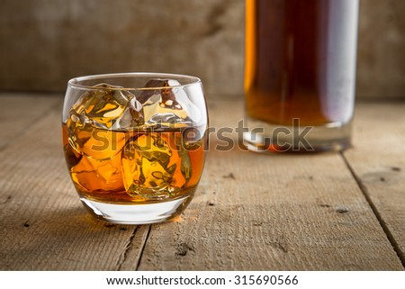 Whisky glass and bottle golden brown ice on wooden surface in saloon bar pub - stock photo