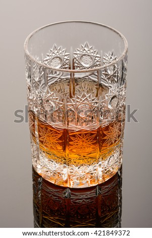 Whisky in beautiful patterned glass on mirror surface. Whiskey macro