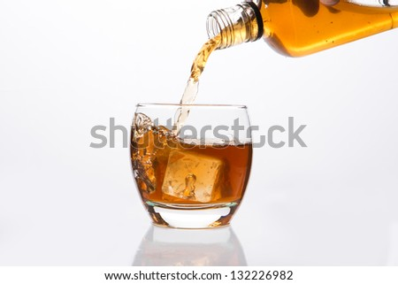Whisky pouring into glass on white background - stock photo
