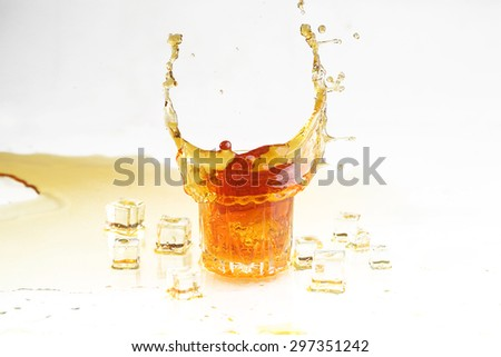 Whisky splash in a transparent glass and ice slices on a white background, dynamics of a liquid