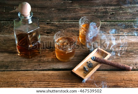 Whisky with ice and cigar on wooden table
