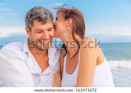 whispering beach couple lovers on blue coast - stock photo