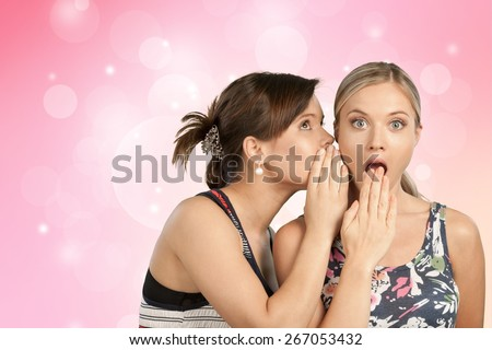 Whispering. Two young woman gossiping - stock photo
