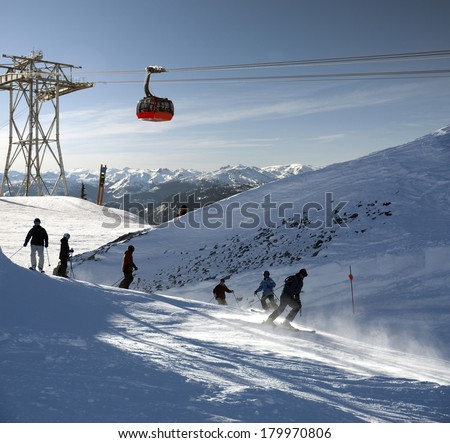 Whistler - mountain scene with unidentified silhouettes of skiers - stock photo