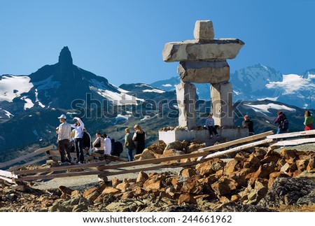 WHISTLER MOUNTAIN - SEPT. 23, 2006: Illanaaq Inukshuk, the symbol of 2010 Winter Olympic Games, Vancouver on the peak of Whistler Mountain, British Columbia, Canada. Black Tusk peak in the background. - stock photo