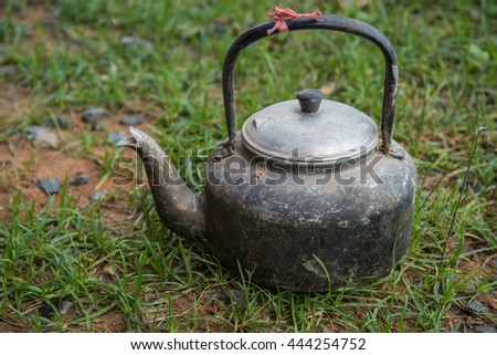 whistling kettle on a green grass, still life with old aluminium, Select focus kettle. - stock photo