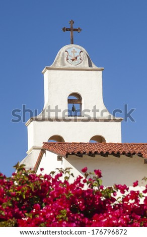 White Adobe Cross Steeple Bell Mission Red Bougainvillea Santa Barbara California.  Founded in 1786 at the end of Father Junipero Serra life. - stock photo