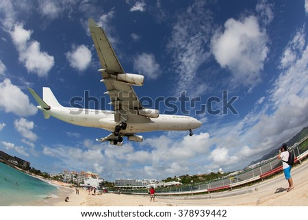 White aircraft in the blue and cloudy sky. Landing near the beach. - stock photo