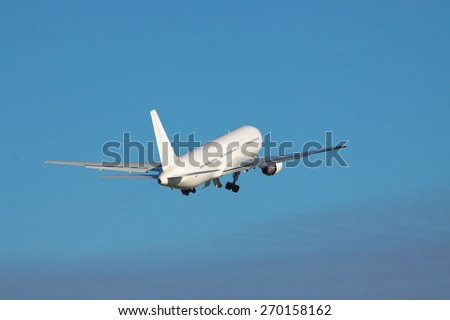 White airplane is taking off to the blue sky - stock photo